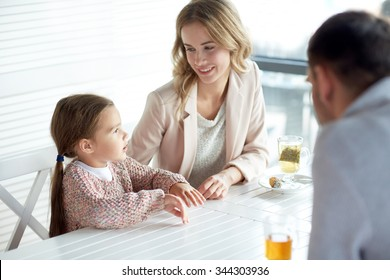 family, parenthood, communication and people concept - happy mother, father and little girl having dinner and talking at restaurant or cafe