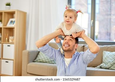 family, parenthood and fatherhood concept - happy father riding little baby daughter on his neck at home