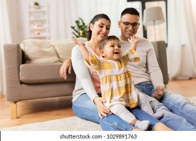 family, parenthood and people concept - happy mother, father and baby daughter playing at home