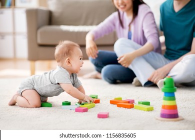 family, parenthood and people concept - happy mother, father and baby boy playing toy blocks at home