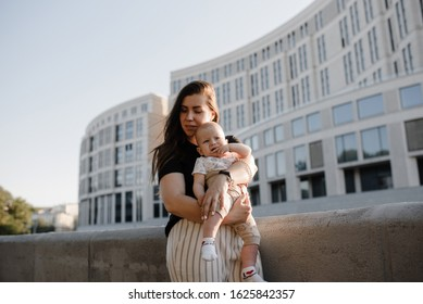 Family, parenthood and people concept - happy motherwith baby walks on a city street . 5 months old baby.