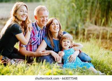 Family Parenting Love Togetherness Happiness Summer Concept. Happy parents with two daughter relaxing and having fun on the lake shore
