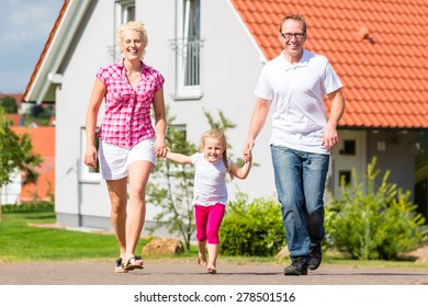 Family of Parents and child walking in front of home in village or suburb