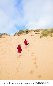 The family, parents and children are climbing the sand dune. Family weekend.