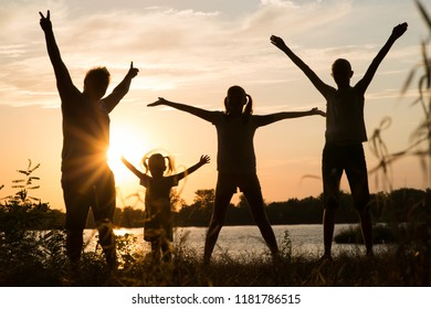 Family of parents and children silhouettes at sunset outdoors
