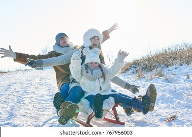 Family with parents and daughter playing toboggan in winter with enthusiasm