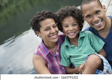 A family, parents and a young boy, by a lake in summer.