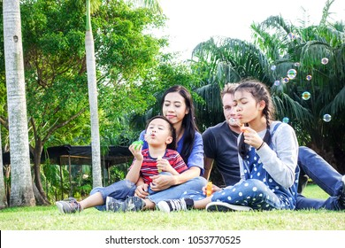 Family in park blowing bubbles together. White blond man, chinese woman, chinese boy and girl sitting in park together. Family fun concept.
