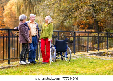family in the park with handicapped daughter with crutches and wheelchair