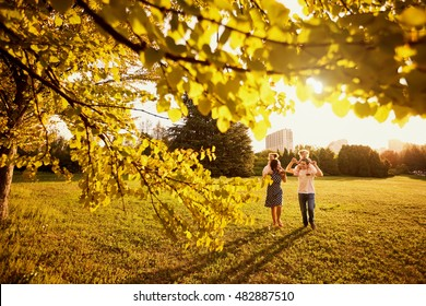 The family in the park. Happy parents with children walk in the nature in the evening at sunset.
