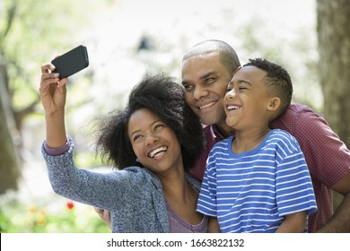 A family in the park on a sunny day. Two adults and a young boy taking photographs with a smart phone.