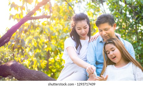 Family in the park. Parents hug each other, look happy and be a warm family.On the day that the sky is bright and the sun is light.