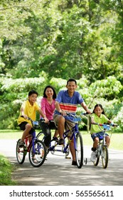 Family in park, riding bicycles