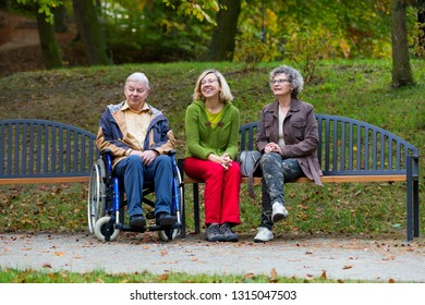 family in the park sitting on a bench with man on wheelchair and talking