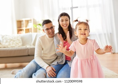 family and people concept - happy little daughter with mother and father at home