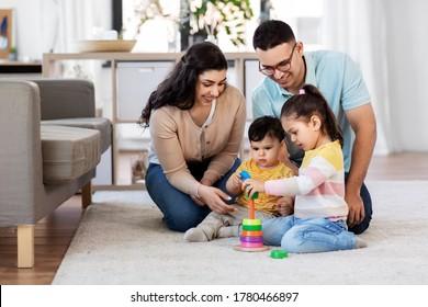 concepto de familia y gente - madre feliz, padre, hija pequeña e hijo bebé jugando con juguete piramidal en casa