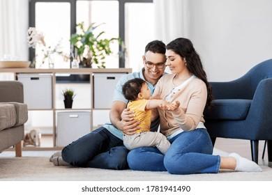 concepto de familia y gente - madre feliz, padre e hijo pequeños sentados en el suelo en casa