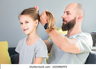 Family and people concept.Cute little daughter and her bearded dad are playing together.Devoted and focused dad is doing his daughter's hair. Family fun and togetherness.Close-up shot