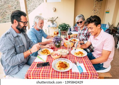 Family people outdoor lunch together on a red table - mixed ages generations enjoy and have fun with italian pasta on the terrace at home - father grandfather and son