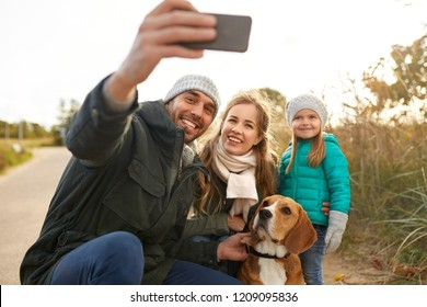 family, pets and people concept - happy mother, father and little daughter with beagle dog taking selfie by smartphone outdoors in autumn
