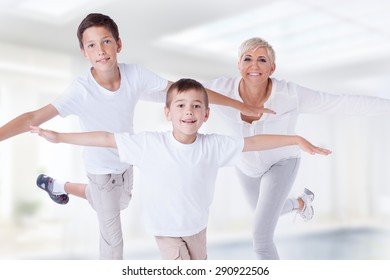 Family photo. Beautiful blonde mother exercising with two young sons, smiling.