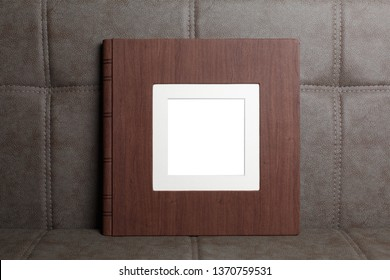 Family photo book with embossing. Photo book on a light background. Brown  photo book with  leather cover. Photoalbum with a hard cover on a wooden background. Wedding photo album.