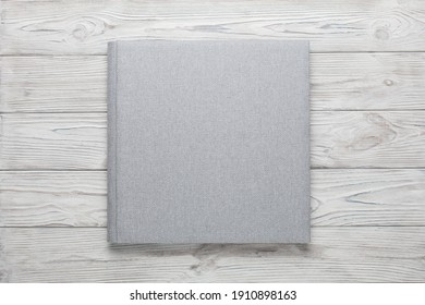 family photo book with grey fabric cover. stylish wedding photo album on wooden background isolated with space for text. light photobook close up. family photoalbum  with beautiful texture cover