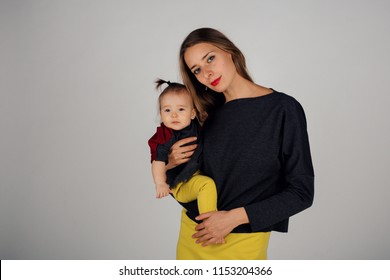 family photo: a woman holding a child in her arms. Fashion for the whole family: mother and daughter dressed in yellow, gray, red. Model shows clothes