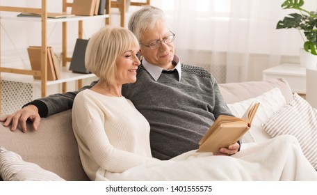Family Photoalbum. Elderly Couple Looking At Photos, Having Rest At Home