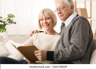Family photoalbum. Senior couple looking at photos, having rest at home