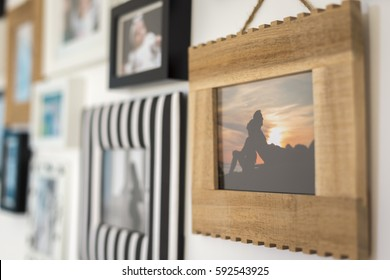 family photos in different frames on a wall