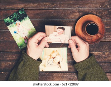 Family photos in man hands and on weathered wooden table. Father drinking coffee and watching family pictures. Top view.