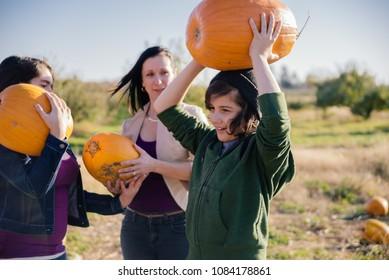 Family picking pumpkins at u-pick farm.