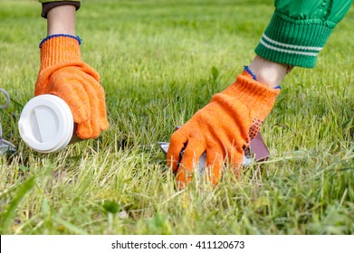 Family picking up trash in spring park wearing protective gloves, focus on boy hand with plastic glass