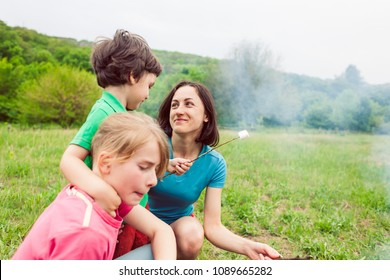 Family picnic. Children with their mother fry marshmallows on skewers. Family holiday in nature. A boy with his parents and brother bake marshmallows on fire.
