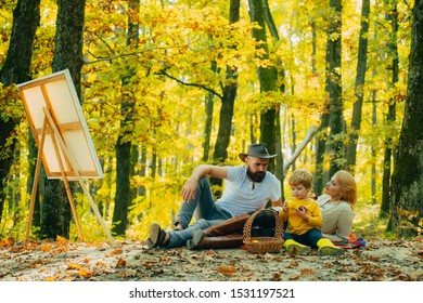 Family picnic. Mother, father, son drawing pictures together in green park. Family day, family activities in nature. Having a snack-time. Apples for lunch. Education outdoors