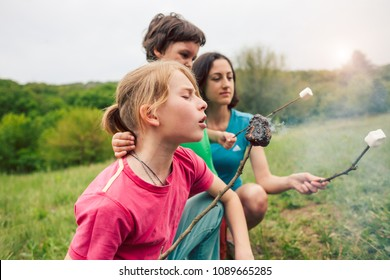 Family picnic in nature. Children with their mother fry marshmallows on skewers. A boy with his parents and brother bake marshmallows on fire. The boy looks at the burning sweetness and laughs.