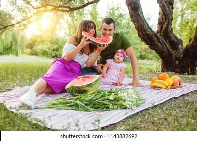 Family at picnic. Parents eating a watermelon. Baby girl looking at camera.