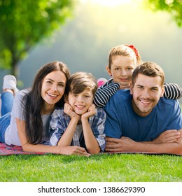 Family at Picnic. Portrait of happy smiling young parents and two children, lying together on a picnic blanket, at sunny day, outdoor. Love, family and happy childhood lifestyle concept photo.