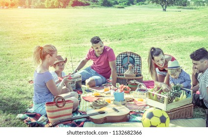 family picnic with two kids or infants. young multicultural parents sitting on meadow with children having a meal with healthy fresh fruits. also a guitar and a ball in the scene.