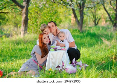 Family picnicking in the garden celebrates birthday