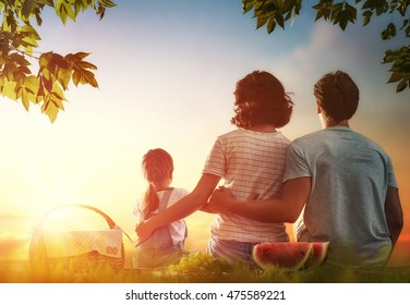 Family picnicking together. Young mother, father and child daughter girl sitting together on green grass in summer park.