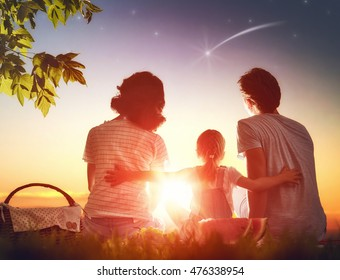 Family picnicking together. Young mother, father and child daughter girl sitting together on green grass in summer park and making a wish by seeing a shooting star.