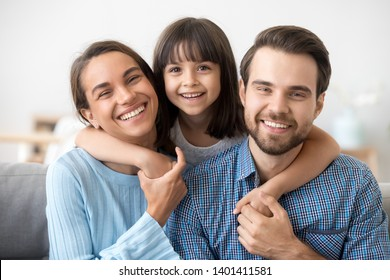 Family picture of smiling young mom and dad sit on couch posing with cute little daughter, small excited funny preschooler girl hug happy parents, relax on sofa look at camera making photo together