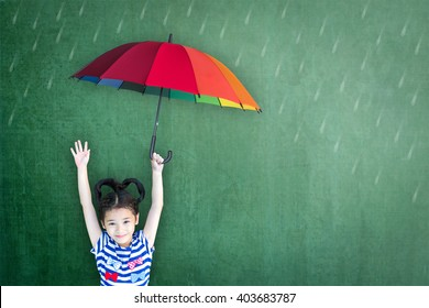 Family plan for child education and insurance protection concept with student holding umbrella on chalkboard