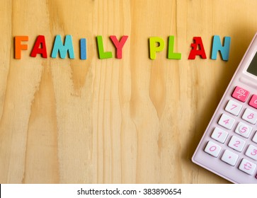 Family planning text with pink calculator on wood table backgound