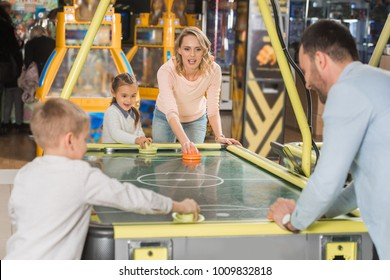 family playing air hockey together in entertainment center