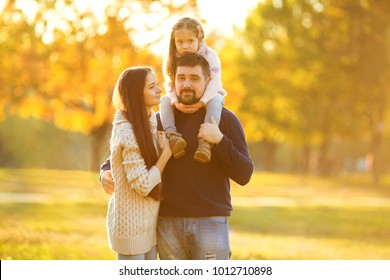 Family playing in autumn park having fun