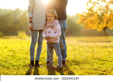 Family playing in autumn park having fun at sunset