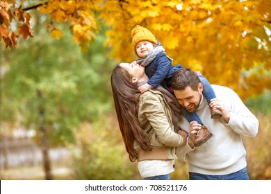 Family playing in autumn park having fun